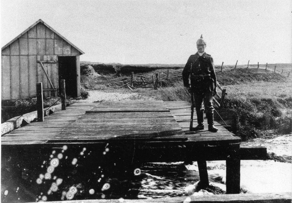 Frihedsbroen med tysk grænsegendarm, 1914. For at ingen skal krydse broen illegalt er en del broplanker blevet fjernet. Foto: Vejen Lokalhistoriske Arkiv.